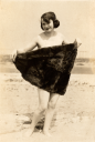 Royalty Free Photo of a Woman Holding Up a Towel at the Beach