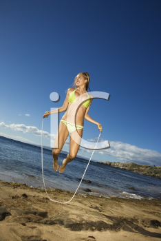 Royalty Free Photo of a Woman in a Bikini Jumping Rope on a Beach in Maui Hawaii