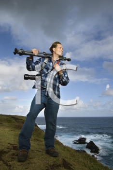 Caucasian mid-adult man standing with camera and tripod over his shoulder on cliff overlooking ocean in Maui, Hawaii.