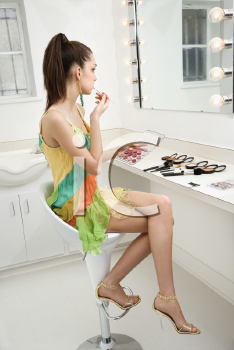 Royalty Free Photo of a Woman Applying Makeup Looking in the Mirror