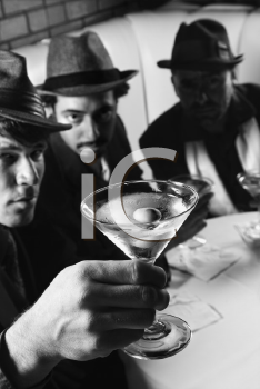 Royalty Free Photo of Three Men Sitting in a Bar With Martinis