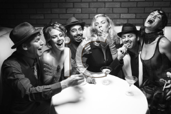 Royalty Free Photo of a Group of Males and Females Sitting at a Table in the Lounge Laughing
