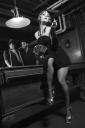 Caucasian prime adult female standing in front of pool table with two Caucasian prime adult men in background.