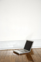 Royalty Free Photo of a Laptop on a Hardwood Floor