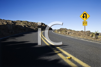 Royalty Free Photo of a Road and Curve in a Road Sign in Haleakala National Park, Maui, Hawaii