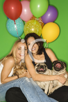 Royalty Free Photo of Women Sitting With Their Dogs and Balloons