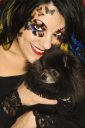 Royalty Free Photo of a Woman in Unique Makeup Holding a Black Pomeranian Dog