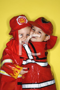 Royalty Free Photo of Twin Boys Dressed as Firemen Hugging
