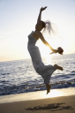 Royalty Free Photo of a Bride Jumping on the Beach