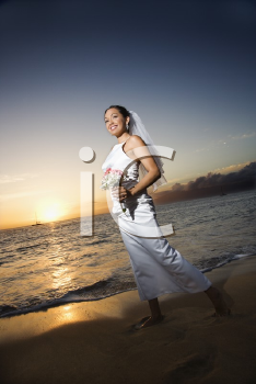 Royalty Free Photo of a Bride at Sunset Holding a Bouquet on a Beach