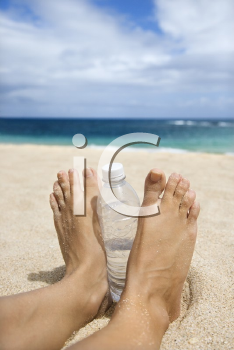 Royalty Free Photo of a Caucasian Woman's Feet and Water Bottle on the Beach