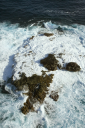 Royalty Free Photo of an Aerial View of Rocks in the Pacific Ocean With Water Swirling Around Them off the Coast of Maui, Hawaii
