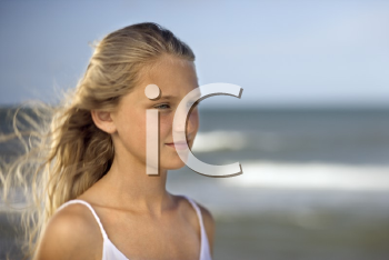Royalty Free Photo of a Preteen Girl on a Beach With Ocean Waves in the Background