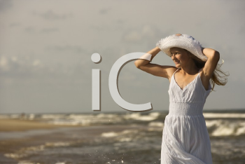 Royalty Free Photo of a Preteen Girl Standing on a Beach Holding Her Hat on Head