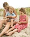 Caucasian mid-adult woman sitting with male toddler on lap and beside Caucasian female child on beach  looking at shells.