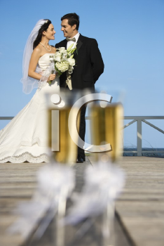 Royalty Free Photo of a Pair of Flute Glasses of Champagne With a Bride and Groom in the Background