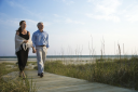 Royalty Free Photo of a Couple Holding Hands and Walking Down a Walkway at a Beach
