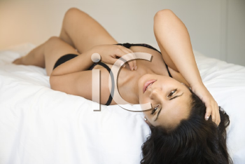 Royalty Free Photo of a Woman in Lingerie Lying on Bed With Her Hand in Her Hair