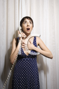 Royalty Free Photo of a Woman Holding a Telephone Receiver to Her Ear Looking Shocked