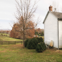 Royalty Free Photo of a House in a Rural Setting in Autumn With a Standing Oil Tank Outside