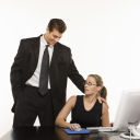 Caucasian mid-adult man touching shoulder of woman sitting at computer who feels uncomfortable.