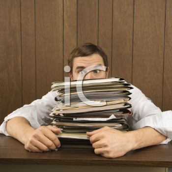 Royalty Free Photo of a Man Peeking Over a Stack of Paperwork