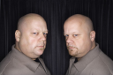 Caucasian bald mid adult identical twin men looking sternly at viewer.