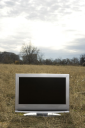 Royalty Free Photo of a Flat Panel Television Set in a Grassy Field