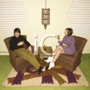 Royalty Free Photo of a Couple Seated in Retro Chairs Smiling and Drinking