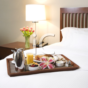 Royalty Free Photo of a Breakfast Tray Laying on a Bed in an Upscale Hotel