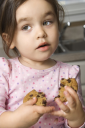 Royalty Free Photo of a Girl Eating a Chocolate Chip Cookie
