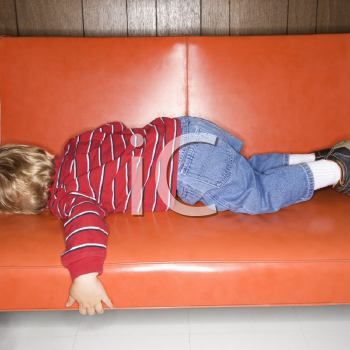 Royalty Free Photo of a Boy Sleeping on a Vinyl Sofa