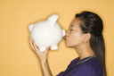 Asian Chinese mid-adult female doctor kissing piggy bank against yellow background.