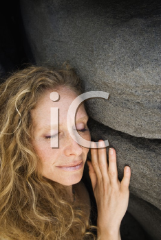 Caucasian mid-adult woman smiling with eyes closed leaning against rock.