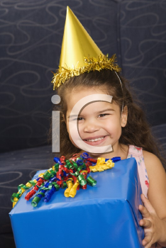 Royalty Free Photo of a Girl Wearing a Party Hat Holding a Birthday Present and Smiling