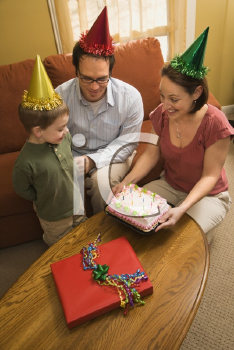Royalty Free Photo of a Boy in a Party Hat Looking at His Birthday Cake