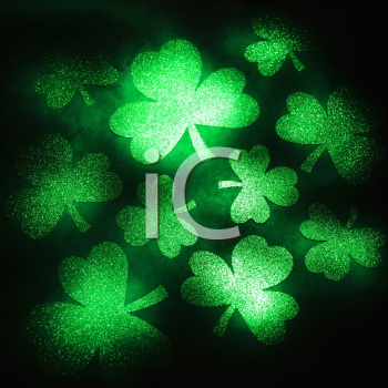 Royalty Free Photo of a Group of Green Shamrocks Reflecting Light on a Black Background