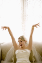 Royalty Free Photo of a Bride on a Love Seat With Arms Raised and Joyful Expression