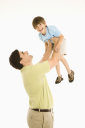 Royalty Free Photo of a Father Holding Up a Boy Overhead