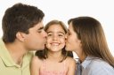 Royalty Free Photo of a Mother and Father Kissing Their Smiling Daughter on the Cheek