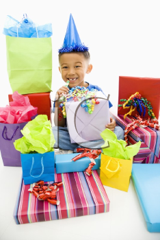 Royalty Free Photo of a Boy Sitting Smiling Wearing a Party Hat With Wrapped Presents