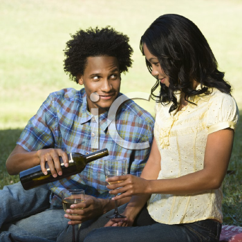 Royalty Free Photo of a Man Pouring a Woman a Glass of Wine While Sitting on a Picnic Blanket in the Park