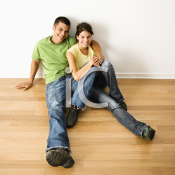 Royalty Free Photo of an Attractive Couple Sitting Close on a Hardwood Floor in Home Smiling