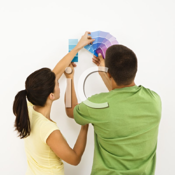 Royalty Free Photo of a Couple Holding Color Paint Samples Up to a White Wall
