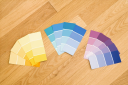 Paint color swatches grouped together by color on wood floor.