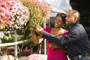 Royalty Free Photo of a Happy Smiling Couple Picking Out Flowers at an Outdoor Plant Market