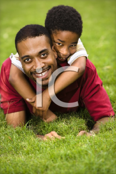 Royalty Free Photo of a Father Lying in the grass Smiling as a Son Climbs on His Back and Hugs His Neck