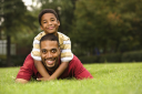 Royalty Free Photo of a Father Lying in the Grass While His Son Climbs on His Back