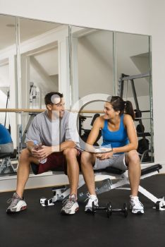 Royalty Free Photo of a Man and Woman Sitting on an Exercise Machine Talking Holding Water Bottles