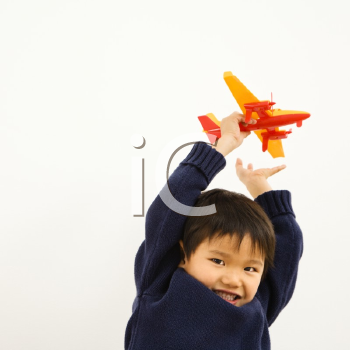 Royalty Free Photo of a Young Boy Playing with a Plastic Toy Airplane